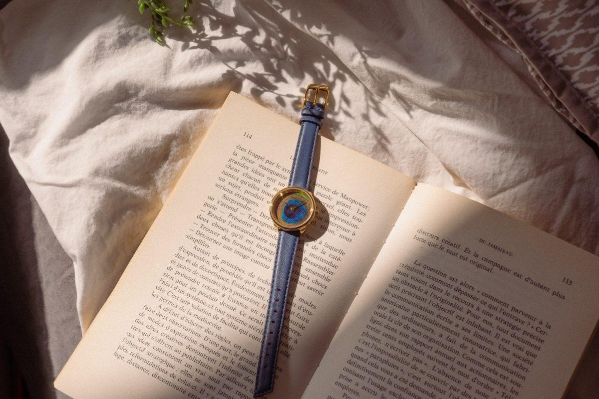 Montre femme originale avec cadran en plume de paon et bracelet en cuir bleu posée sur un livre sur un lit au coucher du soleil