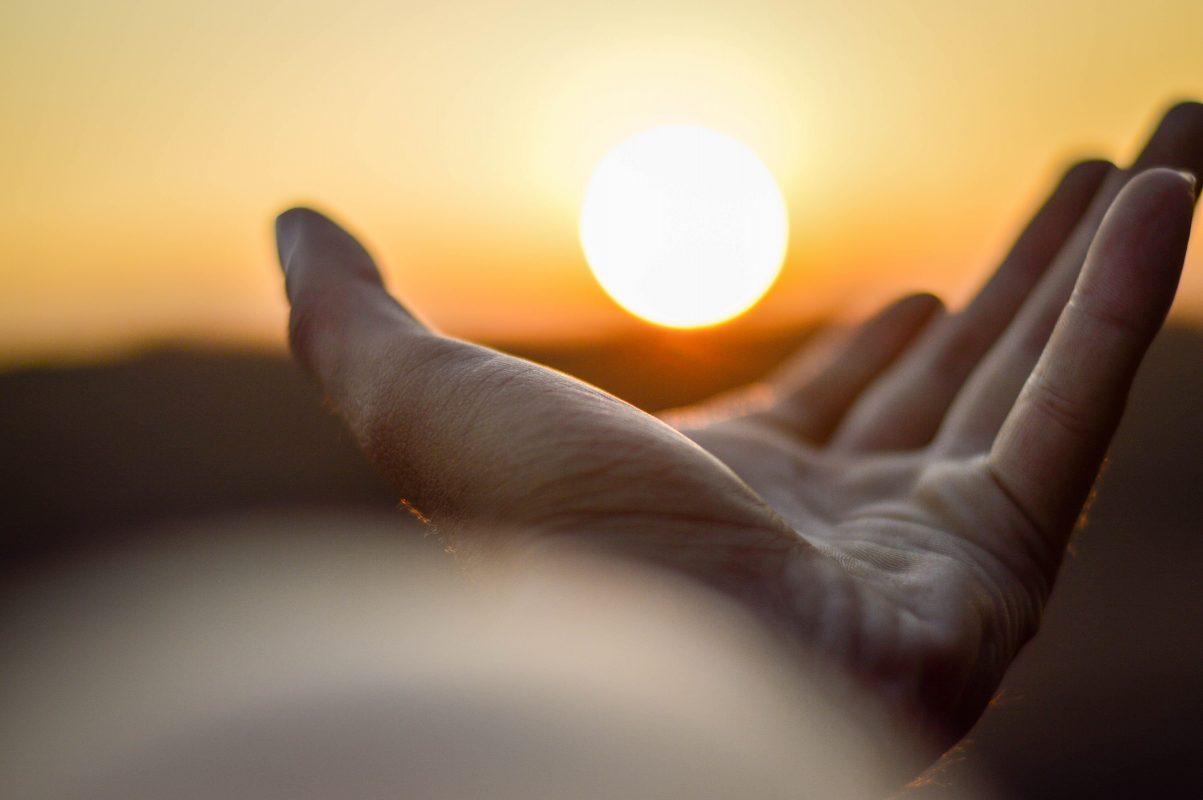 Main tendue vers le coucher du soleil