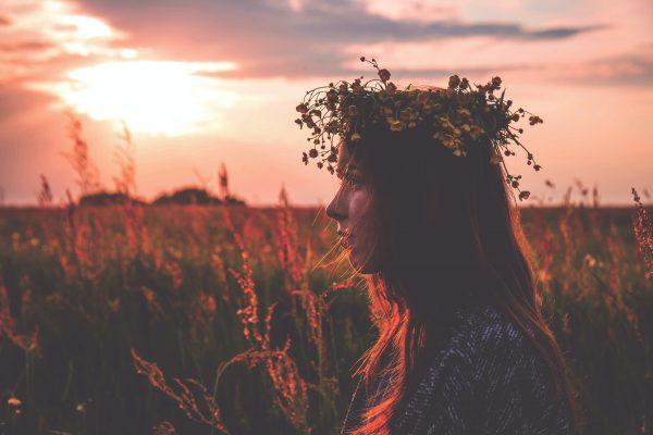 Jeune femme dans un champ portant une couronne de fleurs