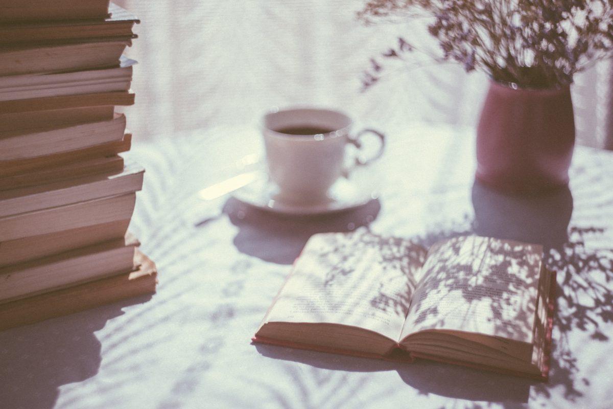 Table ensoleillée avec une pile de livres citations prendre le temps, une tasse de café et un vase fleuri