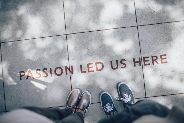 """Couple devant une citation inspirante sur la passion inscrite sur le sol : """"Passion led us here"""""""