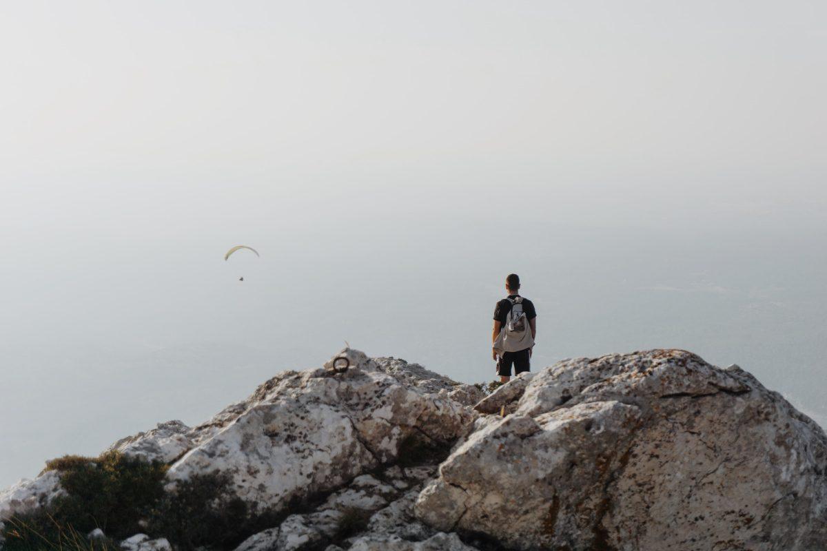 Randonneur en haut d'une montagne avec un parachutiste en plein vol devant lui