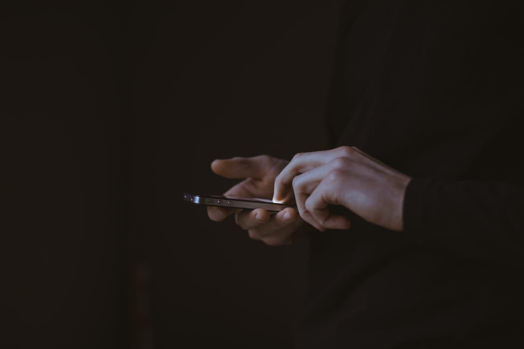 Personne éteignant son téléphone afin de suivre une détox digitale