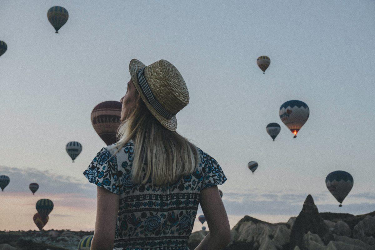Photo inspirante femme devant des montgolfières